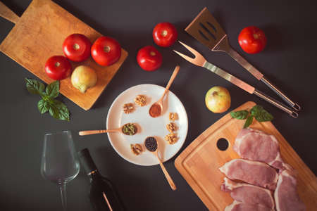 Fresh raw pork meat, spices, bottle of wine, empty wineglass and vegetables on dark background.