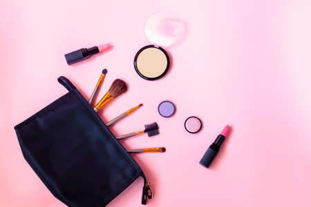Black makeup bag with cosmetic beauty products and make-up brushes on pink background. Top view, copy space.