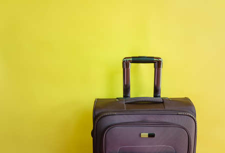 Brown suitcase on yellow background. View with copy space. Stock fotó