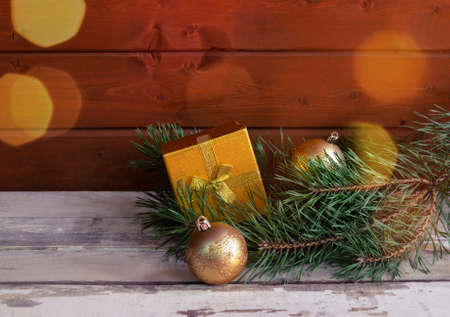 Pine branches, gold christmas balls and gold gift box on wooden background. Selective focus. View with copy space.