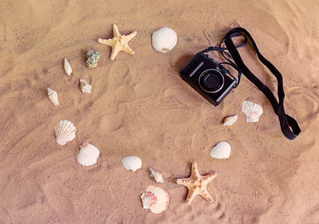 Summer beach holidays concept. Photo camera, starfishes and seashells on sand beach. Top view, copy space.