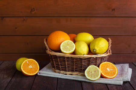 Basket with oranges and lemons on wooden table. View with copy space.