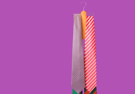 Male ties hanging on the rack. Purple background. View with copy space.