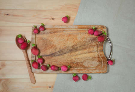 Cutting board, wooden spoon and fresh ripe radish on wooden background. Top view, copy space.