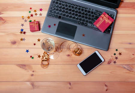 Holidays preparation concept. Laptop, smartphone, glass of champagne and gift boxes on wooden table. Top view, copy space. Standard-Bild - 138450557