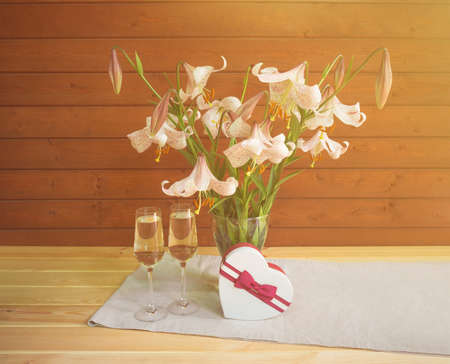 Bouquet of beige colored lilies with pink spots in glass  vase, two glasses of champagne and heart shape gift box on wooden table. Reklamní fotografie