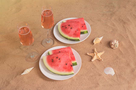 Glasses of rose champagne, plates with slices of watermelon, starfishes and seashells on sand beach. Selective focus.