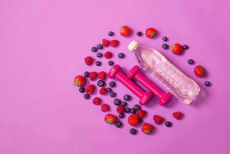 Pink dumbbells, bottle of water and berries on purple background. Healthy eating and fitness concept. Top view, copy space.