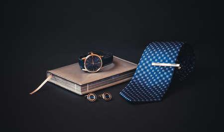 Blue rolled necktie, stylish tie pin, cufflinks, diary and watch on dark background.  Selective focus. Standard-Bild