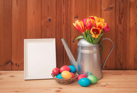 Easter concept. Colorful tulips in watering can, Easter eggs in wicker basket and white frame on wooden table. View with copy space. Standard-Bild