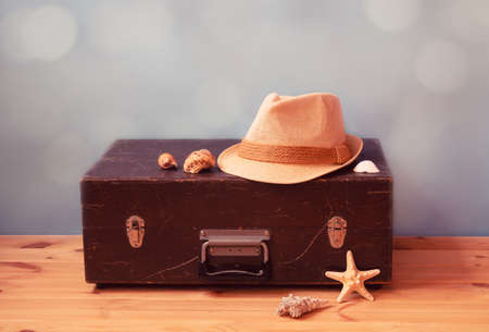 Vintage wooden suitcase, hat, starfish and  seashells on blue background. Summer holidays and travel concept. View with copy space. Standard-Bild
