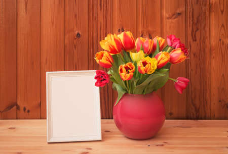White frame and bouquet of fresh tulips in vase on wooden table. View with copy space. Standard-Bild