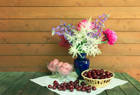 Beautiful bouquet in blue vase, glass bowls with cherry ice cream and basket of fresh cherry on rustic wooden table. View with copy space.