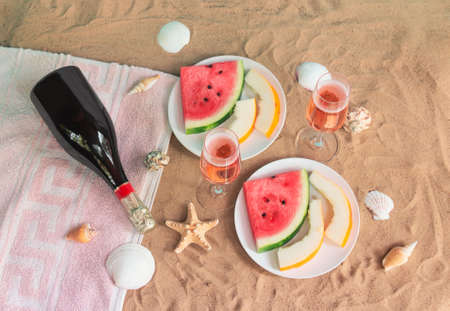 Glasses of rose champagne, plates with slices of watermelon and melon, bottle of champagne, starfishes and seashells on sand beach. Top view. Selective focus.