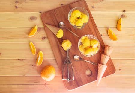 Orange sorbet ice cream,  ice cream cones and fresh oranges on rustic wooden table. Top view.