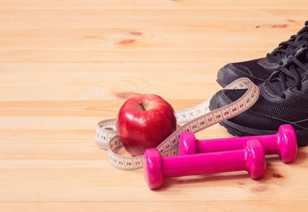 Dumbbells, measuring tape, apple and sneakers. Selective focus. Fitness, healthy and active lifestyles concept. View with copy space.