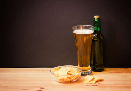 Glass of  beer, bottle of beer and potato chips on wooden table on dark background. Selective focus. View with copy space.