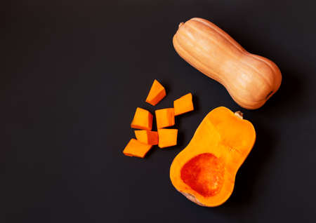 Butternut squash and pumpkin pieces on dark background. Top view, copy space.
