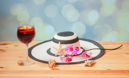 White summer hat, glass of red wine sangria, purple orchid, starfish and seashells on blue background. Selective focus. Beach holidays concept.