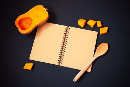Empty notebook, half of butternut squash and pumpkin pieces on dark background. Recipe concept. Top view, copy space.