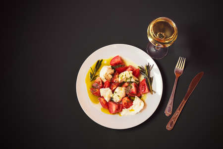 Caprese salad and glass of white wine on dark background. Top view with copy space. Standard-Bild