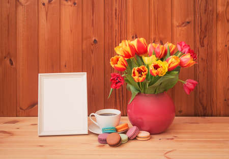 Colorful tulips in pink vase, cup of coffee with macaroons and white frame on wooden table. View with copy space. Standard-Bild