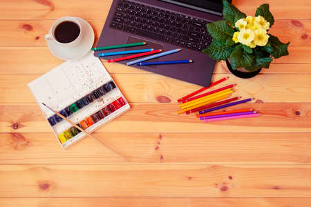 Color pencils, watercolor paints, primrose flower, cup of coffee and laptop on desk. Top view, copy space.