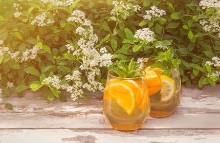 Summer orange lemonade in glasses  on rustic wooden table on fresh white Spiraea flowers background Standard-Bild