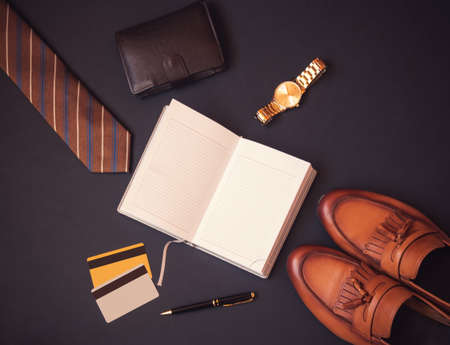 Opened diary, necktie, wallet, watch, credit cards, pen and stylish shoes  on dark background. Top view, copy space.