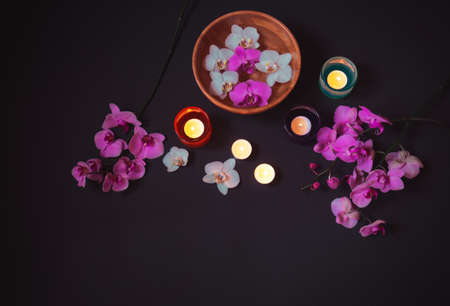 Colorful orchids and burning candles on dark background. Top view, copy space. Standard-Bild