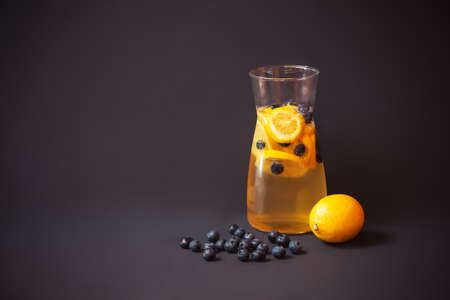Pitcher of summer lemonade with blueberries and lemon, blueberries and lemon near. Dark background. View with copy space.
