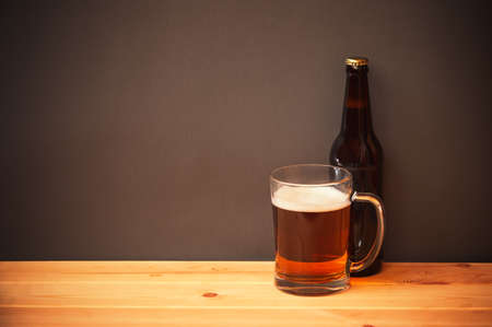 Mug and bottle with beer on wooden table. View with copy space.