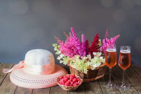 Summer hat, beautiful astilbe and hydrangea flowers, glasses of rose champagne and fresh raspberry on wooden table. Selective focus. Standard-Bild