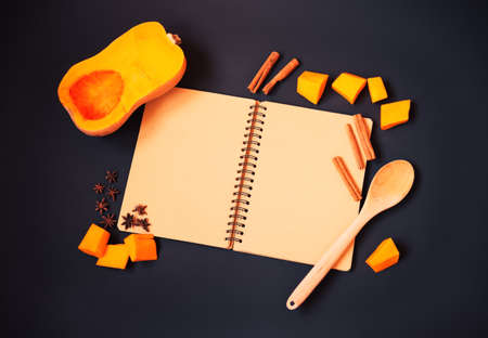 Empty notebook, half of butternut squash, pumpkin pieces and spices on dark background. Recipe concept. Top view, copy space.