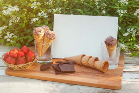 Empty card for your text, waffle cones with chocolate ice cream in  In glasses as stand, pieces of dark chocolate, basket of fresh strawberry and empty waffle cones near on rustic wooden table on fresh white Spiraea flowers background.