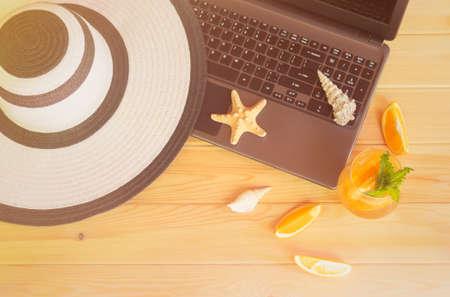 Summer hat, laptop, orange lemonade, starfishes and seashells on wooden table. Summer holidays concept. Top view. Standard-Bild