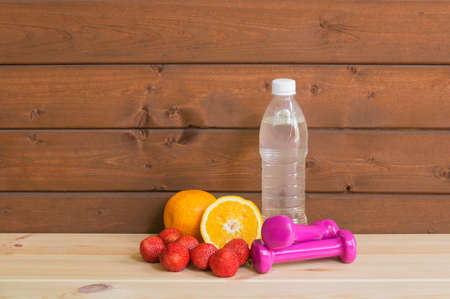 Dumbbells, bottle of water, fresh oranges and strawberry. Fitness and healthy eating concept. View with copy space. Standard-Bild