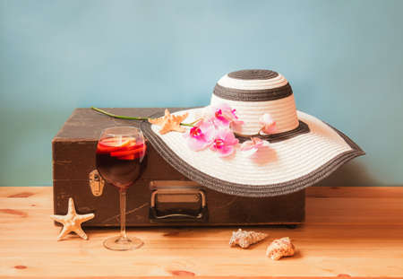 Vintage wooden suitcase, large white hat, glass of sangria, branch of purple orchid, starfish and  seashells on blue background. Concept of summer holidays. Selective focus. View with copy space. Standard-Bild