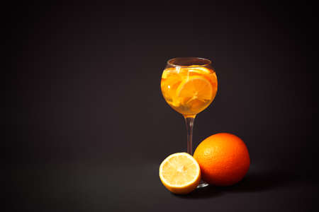 Glass of white wine sangria with orange and lemon, orange and half of lemon near. Dark background. View with copy space.