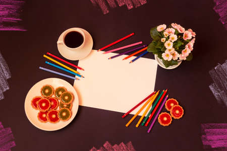 Sheet of blank paper, colourful pencils, cup of coffee, sweet cookies with strawberry jelly and kiwi jelly and primrose flower on dark background. Top view, copy space.