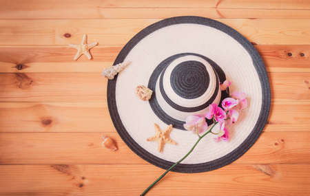 White summer hat  and purple orchid on wooden background. Starfishes and seashells near. Beach holidays concept. Top view, copy space. Standard-Bild