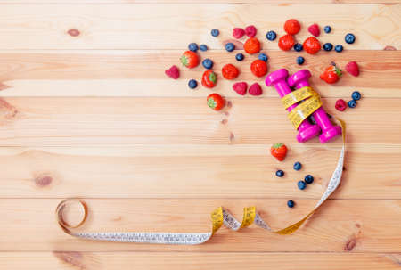 Two pink dumbbells, measuring tape and berries on wooden background. Top view, copy space.
