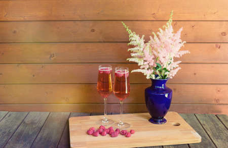 Two glasses of rose champagne, fresh raspberry and astilbe flowers on wooden table. View with copy space.