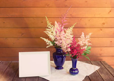 Empty white frame and red, white and pink beautiful astilbe flowers in blue vases on wooden table. Selective focus. View with copy space.