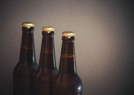Glass bottles of beer on gray background. Selective focus. View with copy space. Standard-Bild