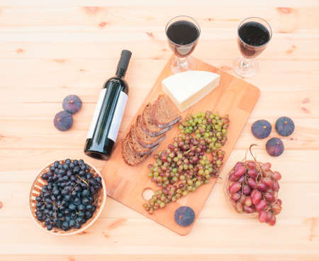 Two glasses of red wine, bottle of red wine, figs, cheese, bunches of grape and bread on wooden table. Top view. Standard-Bild