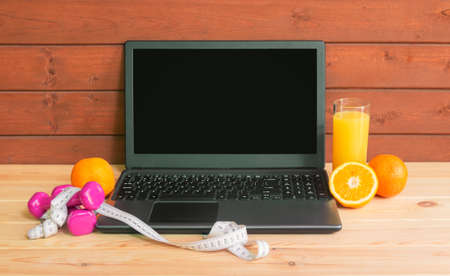 Laptop computer, dumbbells, measuring tape, glass of orange juice and fresh oranges. Exercises, healthy food, online fitness training, staying fit at home. View with copy space. Standard-Bild