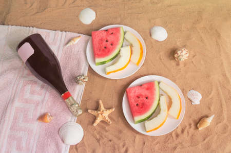 Two plates with slices of watermelon and melon, bottle of champagne, starfishes and seashells on sand beach. Top view.