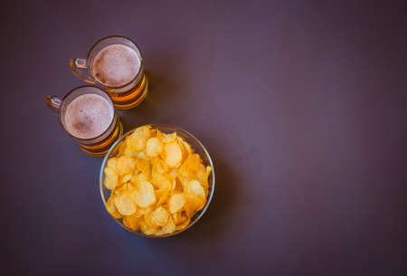 Mugs of beer and bowl with potato chips on gray background. Top view, copy space. Standard-Bild