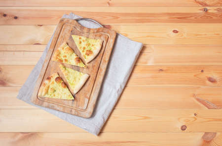 Pieces of wheat focaccia bread with aromatic pesto sauce on cutting board on wooden table. Top view with copy space.